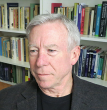 a headshot of Steve Crowell with a slight smile, and a bookshelf in the background